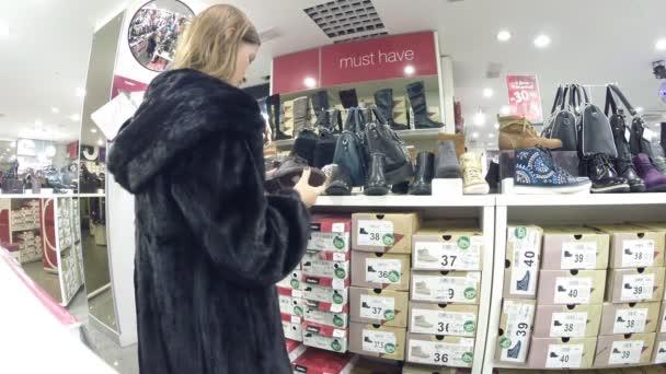 Dívka v obchodě vybírá boty Centro v Ufa, Rusko