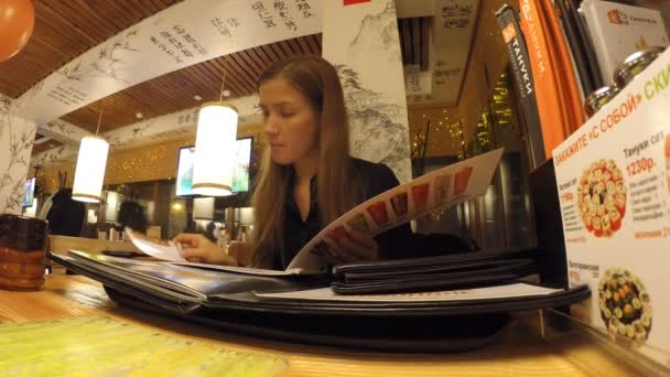 The girl is studying in the menu Japanese restaurant