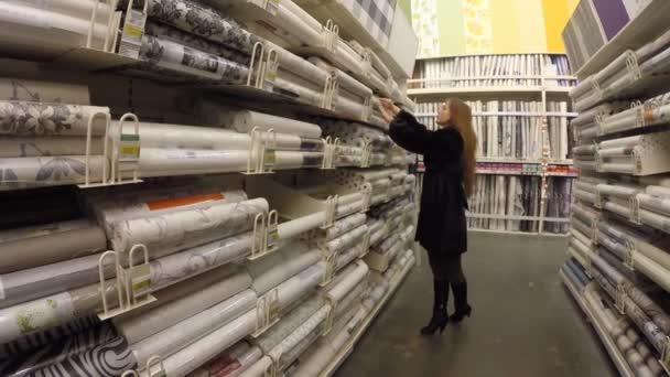 Girl chooses wallpaper store Leroy Merlin