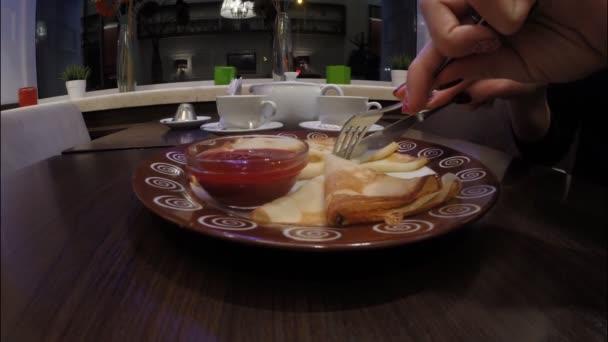 Dívka jí lívance s malinovou marmeládou v café restaurant