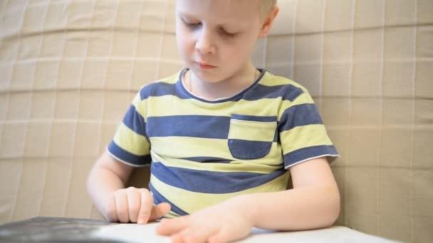 Junge 5 Jahre lesen ein Buch zu Hause auf der Couch