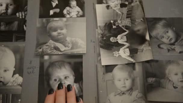 Žena sleduje staré fotoalbum s fotografiemi dětí (kojenců) SSSR