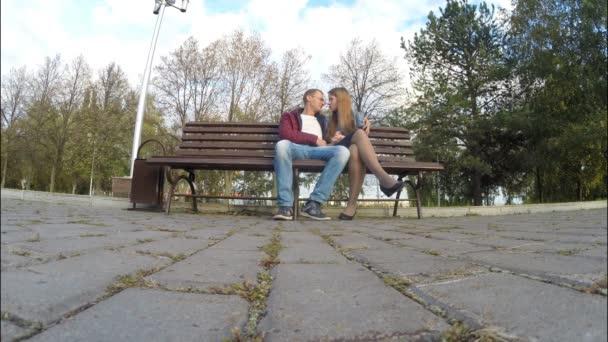 Muž a žena v podzimním parku na lavičce