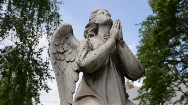 Postava anděla na náhrobní kámen (památník) na hřbitově na pozadí modrého nebe