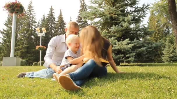 Šťastná rodina se synem v parku, čtení knihy na procházce