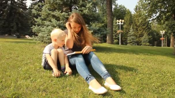 Mladá matka se svým synem v parku, čtení knihy na procházce