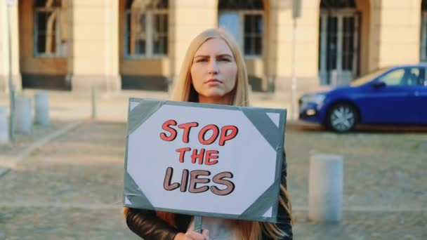 Concerned woman with protest banner calling to stop lies
