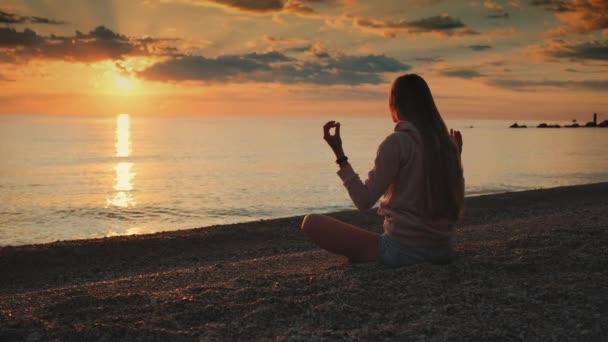 Dívka s meditací nad mořem před západem slunce