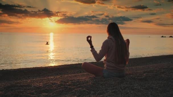 Dáma má meditaci nad mořem před západem slunce