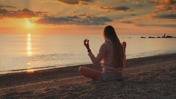 Žena má meditaci nad mořem před západem slunce