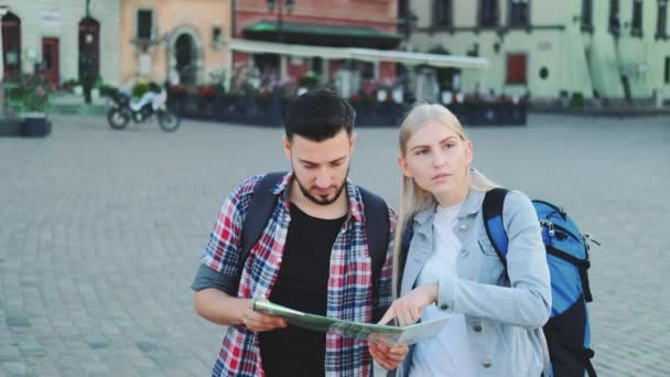 Young couple of tourists with map looking for new historical place in city center