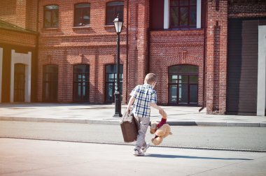 little kid with suitcase and teddy bear toy crossing the sunny s