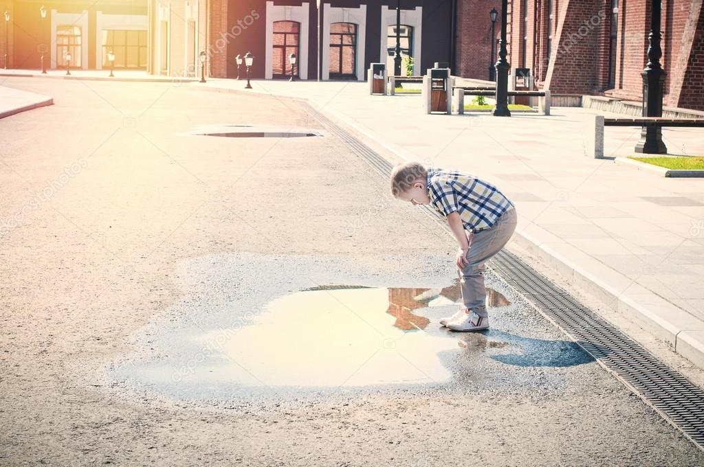 Little boy is looking at the puddle