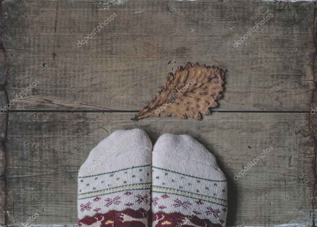 Legs in knitted woolen socks and oak leaf