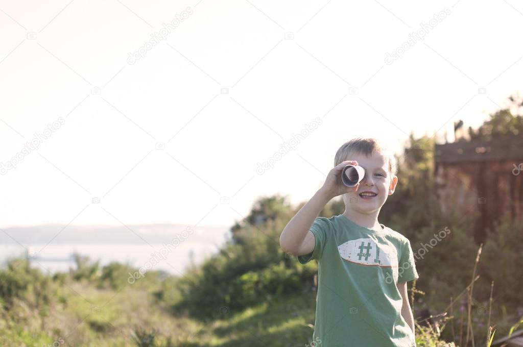 little child playing pirate, looking at spyglass made from cardb
