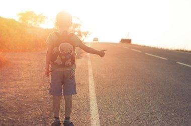 Little child hitchhiking