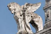 Socha muže drží okřídlený kůň na hlavní nádraží Miláně