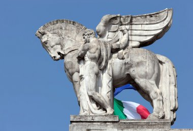 Statue of a man holding a winged horse on the Milan's main railw