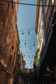 Niedrige Ansicht von Glühbirnen auf Drähten zwischen Gebäuden in Istanbul, Türkei