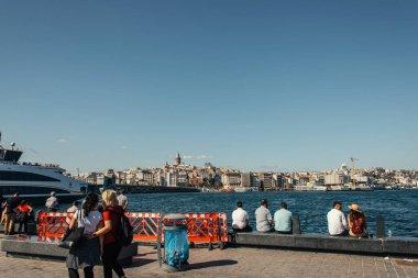 İSTANBUL, TÜRKEYE - 12 Kasım 2020: Kıyı şeridinde, arka planda deniz ve binaları olan insanlar