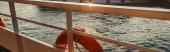 Rettungsring an der Reling des Schiffes mit Meer im Hintergrund, Banner