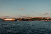 Hajók közelében tengerpart és Isztambul város naplementekor, Törökország