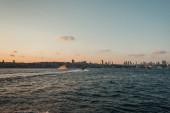Jachta v moři s pobřežím a západem slunce oblohy na pozadí, Istanbul, Turecko