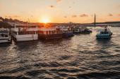 Ukotvené lodě v blízkosti pobřeží a Golden Horn metro most s oblohou západ slunce na pozadí, Turecko