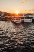 Kotvení roboti v blízkosti budov na pobřeží města a západu slunce oblohy na pozadí, Istanbul, Turecko