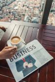 oříznutý pohled na muže u šálku kávy a novin v kavárně s leteckým výhledem na Istanbul