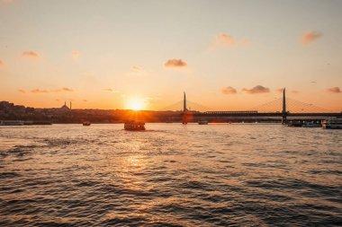 Scenic view of boast in sea, Golden horn metro bridge and sunset sky in Istanbul, Turkey stock vector