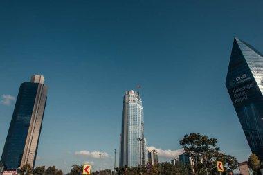 İSTANBUL, TURKEY - 12 Kasım 2020: Modern gökdelenler ve mavi gökyüzüne karşı yeşil ağaçlar