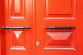 dřevěné dveře, natřené jasně červenou barvou, s kovovými rukojetěmi
