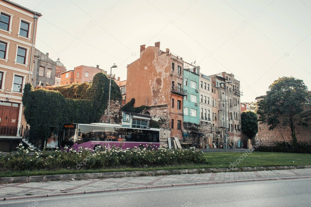 ISTANBUL, TURKEY - NOVEMBER 12, 2020: flowerbed and bus near building, covered with green ivy on street stock vector