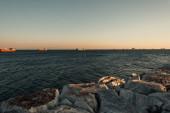 bezmračná obloha nad bárkami na moři a kamenné pobřeží
