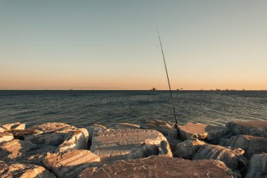 Fishing rod in stones on seashore stock vector