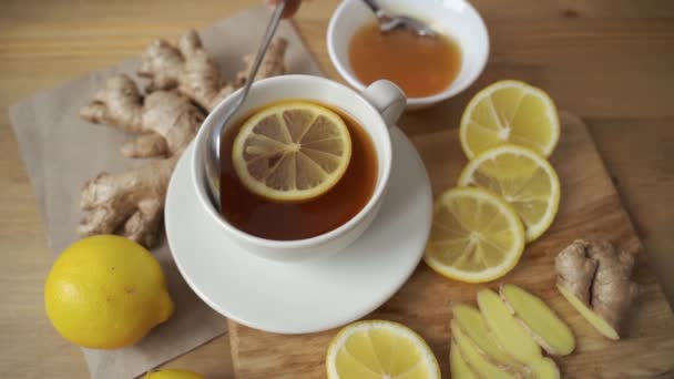 Ginger, lemon, honey, mint, teapot and cup on table