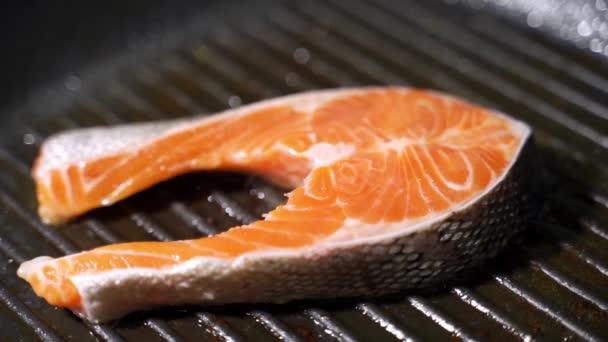 A fűszerek ráesnek a nyers lazac steakre. Nyers lazacvörös hal borssal és sóval.