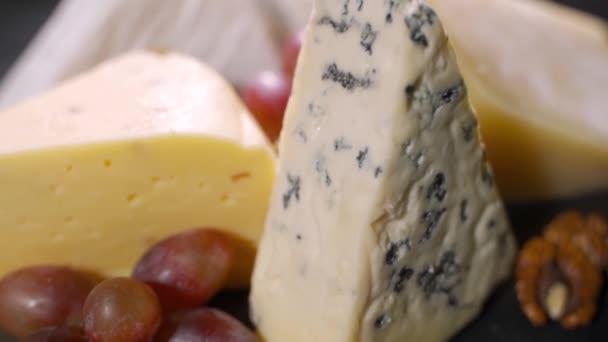 Různé sýry s ořechy a sušeným ovocem na stole. Rotující video