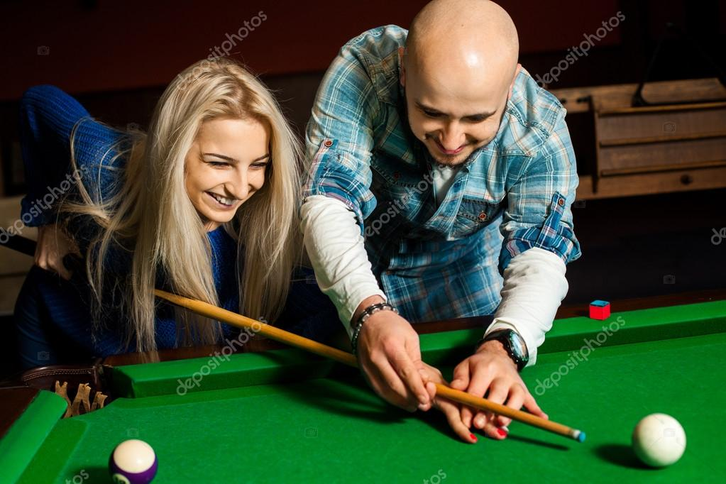 Man Teaches His Girlfriend How To Play On The Pool Table Stock - Games to play on a pool table