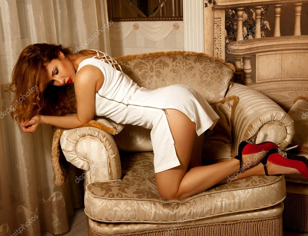 adorable young brunette lady posing doggy style on chair — stock