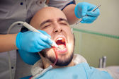 close up photo of handsome guy treats caries teeth in the dental