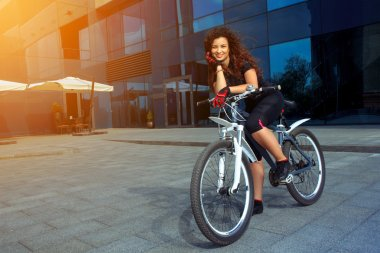 happy brunette sports woman on bicycle