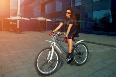 cute brunette sports woman in sunglasses on a bicycle