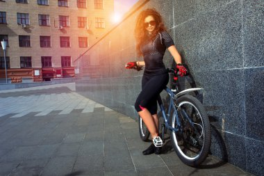 beautiful young woman with curly red hair on bicycle