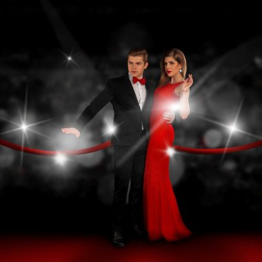 couple on red carpet is posing in paparazzi flashes