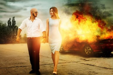 man and a woman go away from burning car