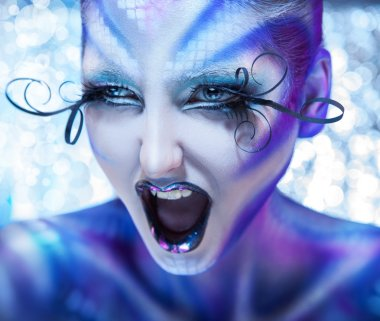 Cute and agry woman screaming. Creative make up on fashion model