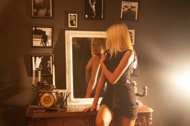 horizontal photo of adorable girl sitting on the nightstand next