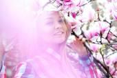 Nádherné mladá blondýna usmívá v růžové kvetoucí květiny